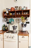 Vintage electric cooker flanked by kitchen base units: wooden shelves of spices and kitchen utensils on wall