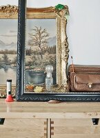 Empty picture frame, vintage objects and gilt-framed oil painting on stripped wood chest of drawers