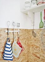 Hand-crocheted pot holders inherited from family and kitchen utensils hung on wall in corner of kitchen with chipboard splashback
