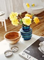 Yellow dahlias in retro ceramic vase in shades of blue and various metal and wood containers on wooden table