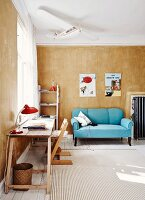 Desk on wooden trestles, Tripp Trapp child's chair, light blue, antique couch in background against vintage-style wall