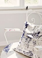 Cushion with blue splattered paint on white background on delicate, vintage metal chair painted white