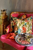 Canapés on silver platter in front of ethnic scatter cushions on deep pink couch