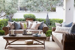 Sofas with wicker frames and scatter cushions around simple wooden coffee table on terrace; low clipped hedge in background