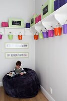 Little boy sitting on giant bean bag in corner below colourful metal buckets hung below white bracket shelves