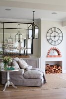 Silver-painted bistro table next to pale chaise, framed mirror on wall, stacked firewood in fireplace and antique wall clock with Roman numerals