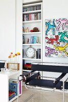 Classic chair below artwork in style of Keith Harings next to shelves in niche with sliding door
