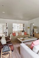 Comfortable living room with pale sofas, pastel scatter cushions and antique, brown leather armchairs