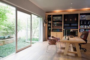 Solid wooden desk and office chair in front of bookcase and opposite glass wall
