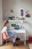 Girl using laptop on desk below floating shelf