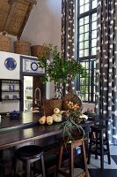Vegetables and baskets on dark wood kitchen counter, bar stools and tall lattice window with floor-length curtains