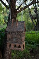 Vintage bird house hung from tree by chains in summery, green garden