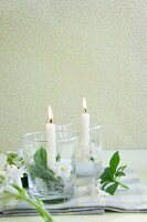 Candles on ice bases and hyacinths flowers in glass lanterns