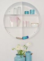 Circular shelving holding china and glasses; white ranunculus in blue enamel churns
