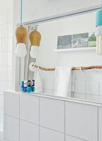Youthful designer lamps, towel rail made from branch and souvenir photos reflected in bathroom mirror