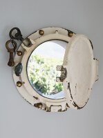 Vintage porthole built into house wall with view into garden