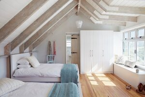 Guest bedroom with twin beds in bright attic room with white-painted wooden beams and parquet floor