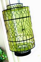 Patterned, wire mesh lantern with green, transparent sheath inside