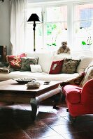 Comfortable lounge area; red armchair and white sofa around wooden table on polished terracotta floor