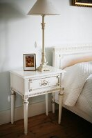 Table lamp on Regency-style bedside table painted white next to bed