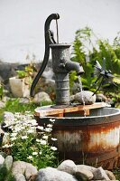 Water feature made from antique hand pump and wooden tub in summery garden