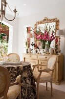 Rococo-style chairs in elegant dining area with vase of gladioli and table lamps on pale wooden cabinet