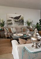 Silver vessel on side table against sofa backrest and picture of aquatic bird on wall in living room with country-house ambiance