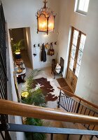 Foyer of country house with animal-skin rug on floor and tall front door with glass panels
