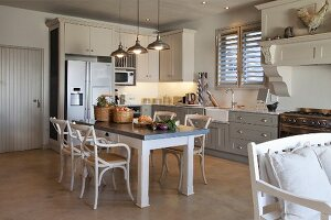 Dining area with white armchairs around table with grey top below row of vintage pendant lamps in open-plan, country-house kitchen