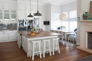 Free-standing island counter and white bar stools in open-plan, country-house kitchen with dining set below window