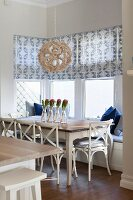 Dining set in window bay with window seat, patterned roller blinds and white-painted chairs