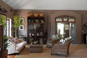 Ottoman between sofa and wicker armchairs in interior in warm earthy shades; ethnic ornaments in and on glass-fronted cabinet