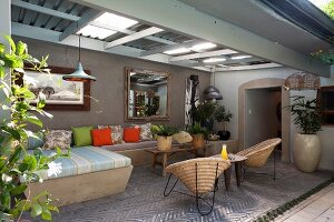 Seating area with masonry benches and wicker easy chairs in roofed courtyard with herringbone brick floor