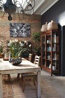 Wooden dining table and simple chairs in front of brick wall and ornate vessels in display cabinet to one side