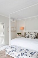 Double bed with white four-poster frame and bench with floral white and blue upholstery at foot in elegant bedroom