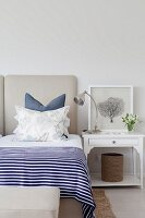Double bed with blue and white striped bedspread, arranged scatter cushions and white-painted bedside table