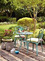 Ornate bistro table and turquoise chairs on rustic terrace seating area