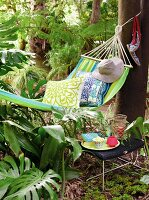 Hammock with cushions and sun hat next to drink on stool