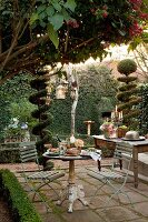 Festively set bistro table on terrace and buffet on table between topiary bushes in garden