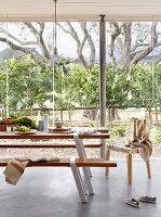 Modern table and bench set on pale grey concrete floor in front of glass wall with view of garden