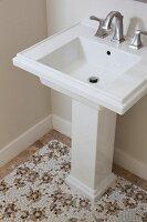 Pedestal washbasin and mosaic floor in bathroom; Irvine; California; USA