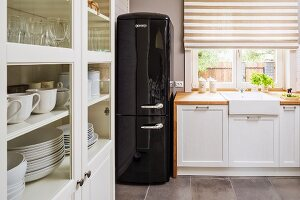 Country-house kitchen with black retro fridge, counter with sink below window and half-closed roller blinds in brown and white stripes; glass-fronted cabinet in foreground