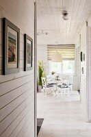 View along wood-clad hallway to dining area below pendant lamps next to window with roller blind