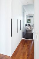 Fitted cupboards in hallway with glass partition wall showing view of sofa in living area