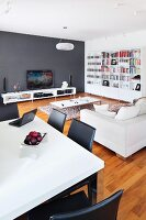 White dining table and black chairs in front of lounge area with sofa and low, white sideboard against dark grey wall