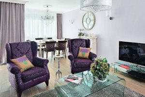 A sitting area in an elegant mix of styles with classically patterned, purple winged armchairs and a modern acyrl table