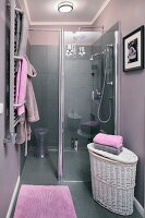 An open shower in an elegant bathroom with grey tiles, lilac-grey walls and lilac coloured towels