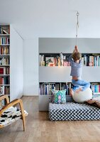 Open-plan interior with child climbing rope suspended from ceiling, black and white patterned futon and partition shelving