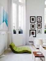 Green futon chair flanked by standard lamps opposite modern table lamp on delicate side table