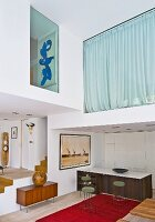 Retro interior, double-height in parts; open-plan kitchen with counter and bar stools, mezzanine with glass walls and closed curtains